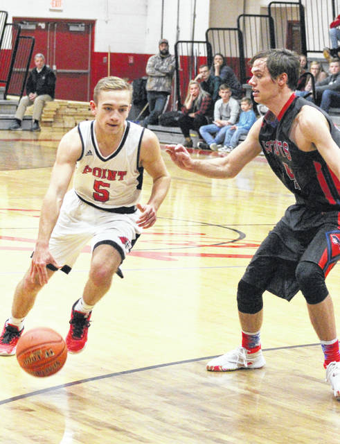 Point Pleasant senior Aidan Sang (5) dribbles past Calvary Baptist defender Robert Clutter during the second half of Thursday night's boys basketball contest in Point Pleasant, W.Va.