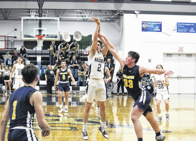 River Valley junior Dylan Fulks (2) hits a buzzer-beating three-pointer over Wellston's Josh Bodey (33) at the end of the third quarter, during the Golden Rockets' 41-38 victory on Tuesday in Bidwell, Ohio.