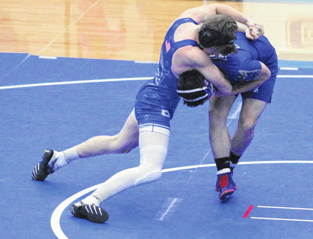 Gallia Academy senior Bronson Carter, left, locks in a hold during on a Warren opponent during his 160-pound match Wednesday night at GAHS in Cenetenary, Ohio.