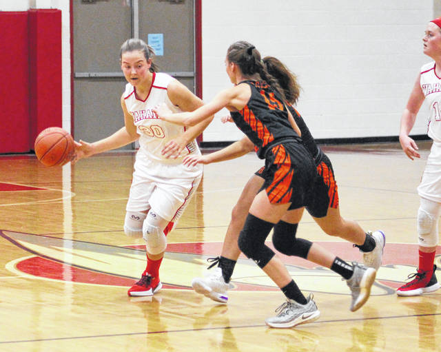 Wahama sophomore Lauren Noble (30) dribbles past a pair of Belpre defenders during the first half of Thursday night's TVC Hocking girls basketball game in Mason, W.Va.