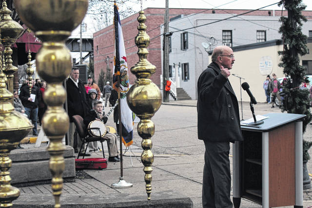 Mayor Brian Billings speaks at Sunday's annual remembrance ceremony honoring the 46 victims of the Silver Bridge Disaster. Benjamin Supple, pictured sitting, provided an instrumental during the reading of the names of the victims.