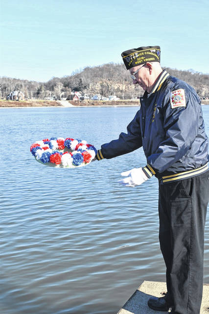 Ronie Wheeler of the Stewart-Johnson post places a wreath in the river during the ceremony.