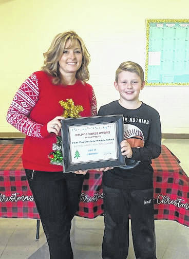 Braydon Sweeney, Toys for Kids member, presents Stacy Walton, Point Pleasant Intermediate School Principal, with the helping hands award. PPIS is the first school that participated school wide in The Light of Christmas tree project at Gunn Park. Each grade level entered a tree, making PPIS the group to raise the most money for Toys for Kids.