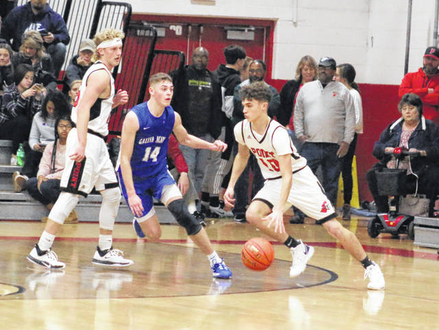 Point Pleasant sophomore Trey Peck (10) dribbles around Gallia Academy defender Logan Blouir during the first half of Saturday night's boys basketball contest in Point Pleasant, W.Va.