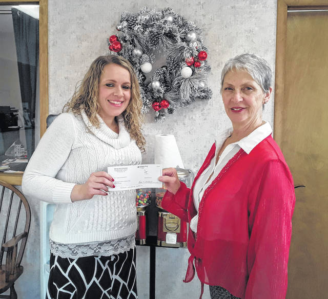 Ashlee Vaughan-Enslen of The Vaughan Agency in Pomeroy presents a check to Vicki Hanson from the Meigs Historical Society. The money received is from a grant provided by MAX, MutualAid eXchange, which was applied for by The Vaughan Agency to benefit the historical society and museum. The money will go to help Meigs County Historical Society buy new computers and help renovate their new building in Middleport.