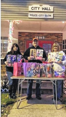 Pictured from left are Lisa Crump, Jason Roush of New Haven Share, and Linda Brewer with the Career Barbies.