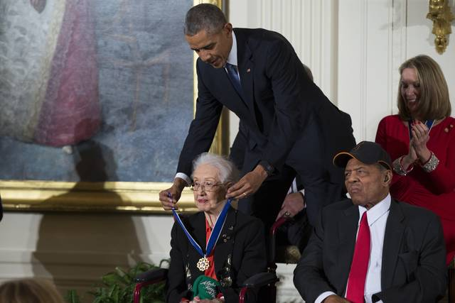 """In this Nov. 24, 2015 photo, Willie Mays, right, looks on as President Barack Obama presents the Presidential Medal of Freedom to NASA mathematician Katherine Johnson during a ceremony in the East Room of the White House, in Washington. Johnson, a mathematician on early space missions who was portrayed in film """"Hidden Figures,"""" about pioneering black female aerospace workers, died Monday, Feb. 24, 2020."""