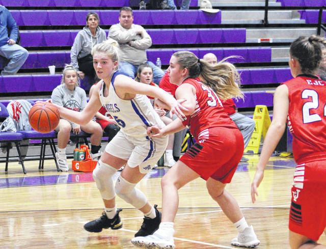 Gallia Academy junior Maddy Petro, left, dribbles around a Jackson defender during the first half of Monday night's Division II sectional semifinal girls basketball contest at Logan High School in Logan, Ohio.