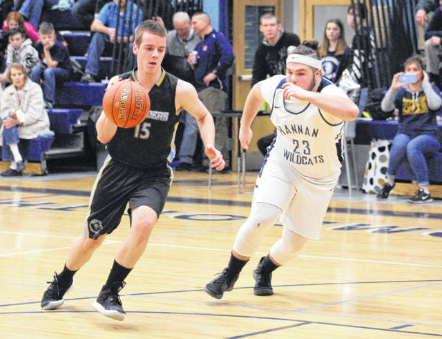 Ohio Valley Christian junior Jeremiah Swab (15) dribbles past Hannan defender Justin Rainey (23) during the first half of Tuesday night's boys basketball contest in Ashton, W.Va.
