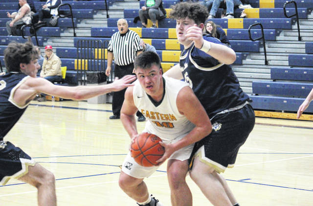 Eastern junior William Oldaker (center) drives between a pair of Titans, during the Eagles' 50-24 victory in Wednesday night's D-4 sectional semifinal in Wellston, Ohio.
