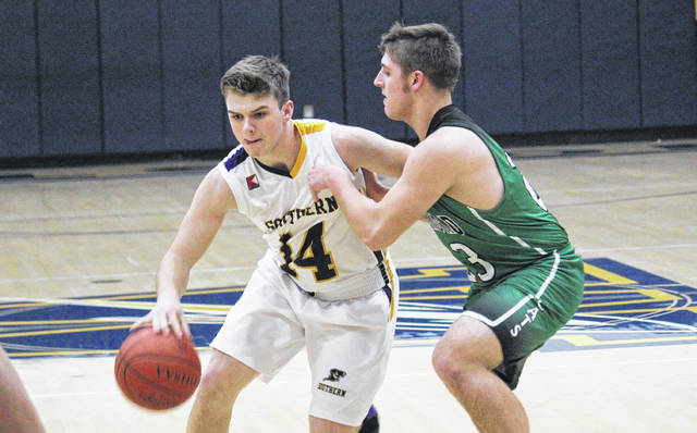 Southern senior Trey McNickle (14) drives past Waterford's Zane Heiss (right), during the Wildcats' 47-42 sectional semifinal victory on Wednesday in Wellston, Ohio.