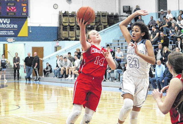 Wahama freshman Amber Wolfe (14) tries a two-pointer in front of PCHS freshman Deborah Hardbarger (23), during the Crusaderettes' 77-48 victory in the Class A Region IV, Section 1 semifinal on Tuesday in Parkersburg, W.Va.