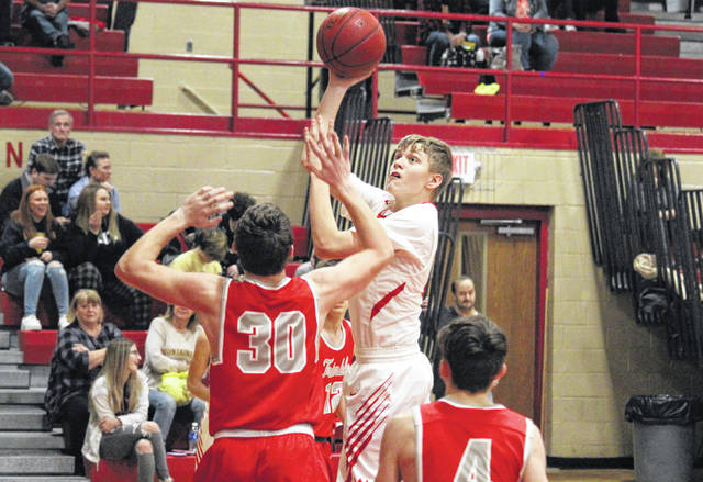 Wahama freshman Ethan Gray tries a two-pointer over Trimble's Bryce Downs (30), during Tuesday's TVC Hocking boys basketball game at Gary Clark Court in Mason, W.Va.