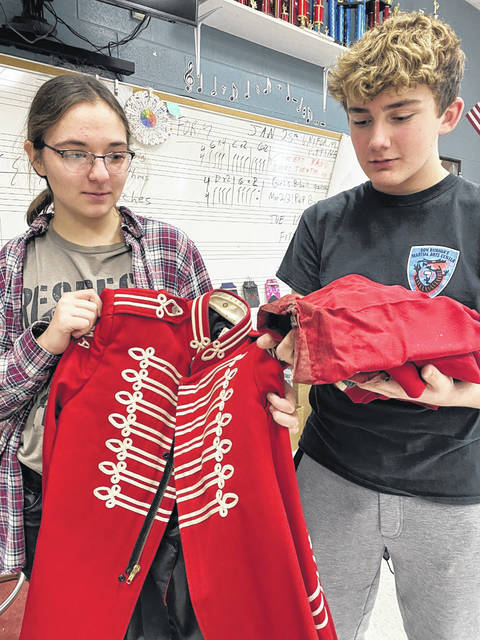 Wahama band members Sydney Burris, left, and Kelsyn Spencer look over a tattered band uniform, purchased in 2004. The band is raising money to finish paying for new uniforms that were recently ordered.