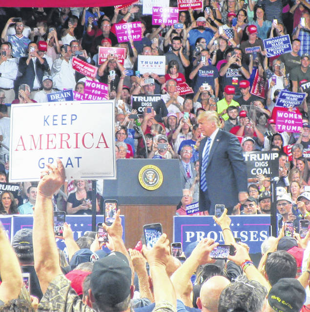 "Supporters waved signs including ""Keep America Great"" as President Donald J. Trump took to the podium at a rally in Charleston in 2018."