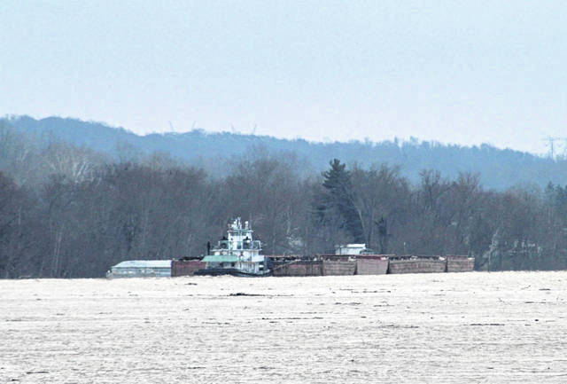 Pictured are multiple barges being held in place Friday morning by this towboat along the Ohio River near Minersville in Meigs County, Ohio, located across from Mason, W.Va. Maritime industry workers in the area attempted to assist and help secure barges that became loose Thursday evening in high water conditions.