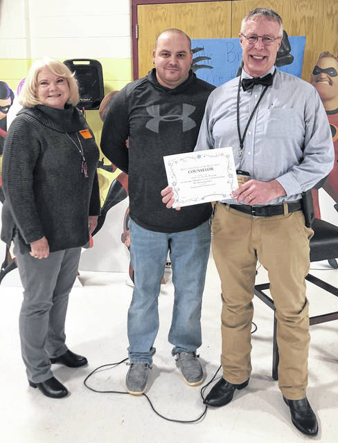 "Jared Billings, Mason County Board of Education president, and Rhonda Tennant, Board member, presents Kim Browning with a proclamation declaring that Feb. 10 ""Mr. Browning Day"" at PPPS."