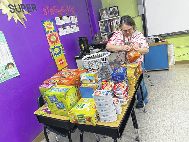 Robin Carter prepares meals for Mason County Schools to send home to students next week.