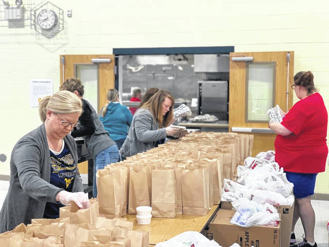 Teachers at Point Pleasant Intermediate School assist service personnel in packing meals for students this week.