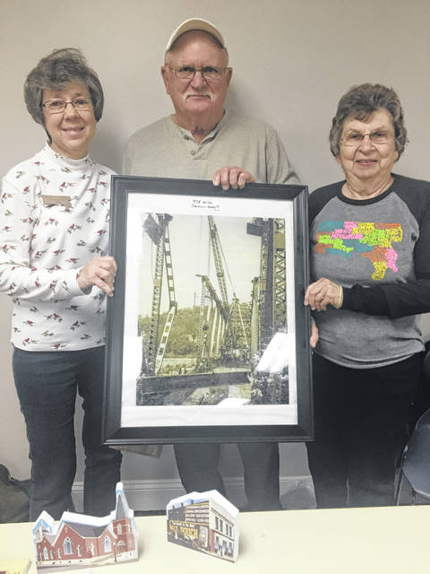 Pictured (from left) are Patty Grosnickle, Bob Graham, and Mary Cowdrey. Grosnickle and Cowdrey accepted the donation of a framed puzzle made from a photograph of the Pomeroy-Middleport Bridge circa 1928 on behalf of the Meigs County History Museum.