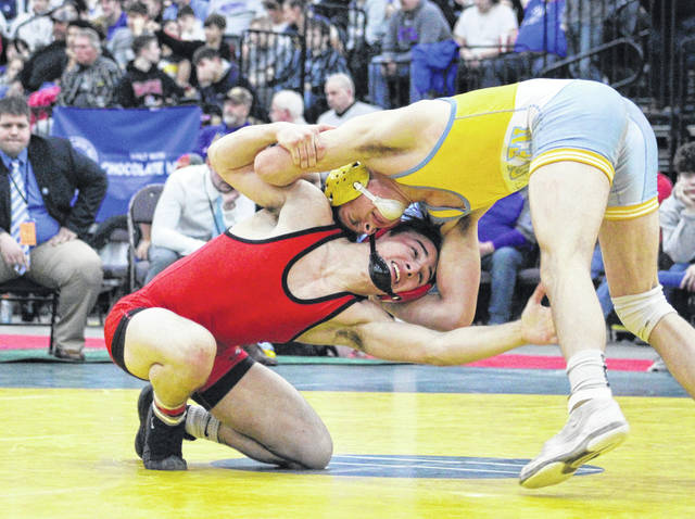 Point Pleasant junior Mitchell Freeman lunges forward to gain leverage on an opponent during the 145-pound Class AA-A championship match Saturday night at Mountain Health Arena in Huntington, W.Va.