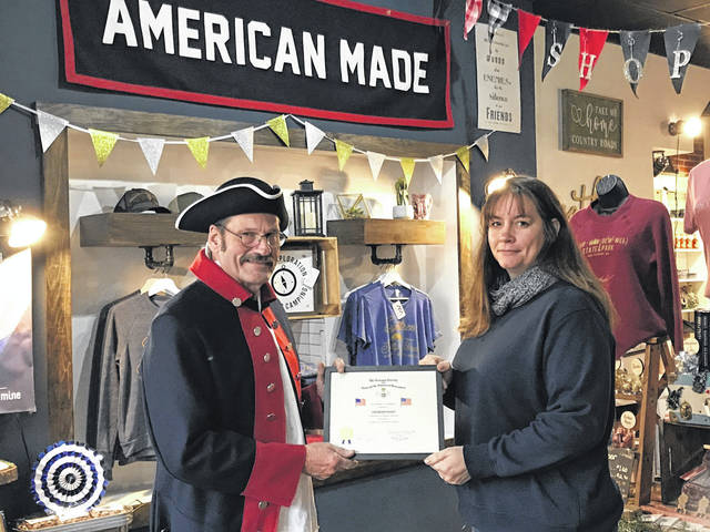 The Sons of the American Revolution present Flag Certificates to businesses and individuals who properly display the nation's colors. Pictured is Point Pleasant SAR Chapter member David Siders presenting Marqkita Sexton, part owner of Counter Point Cooperative, with a certificate. The other owner, Ashley Wamsley, was unavailable for the picture.