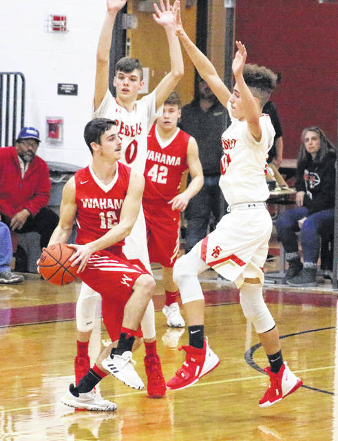 Wahama senior Abram Pauley (12) looks to make a pass while avoiding a double-team during a Jan. 21 boys basketball game against South Gallia in Mercerville, Ohio.