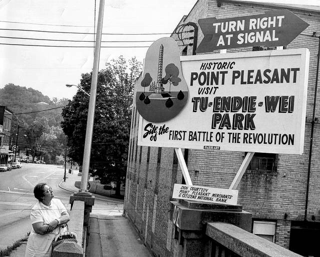 "After weeks of a ""new normal"" the <em>Point Pleasant Register</em> thought it might be a nice change of pace to share a photo from a familiar past. This undated photo appears to have been taken on the ramp to the Silver Bridge. What is now the Mason County Sheriff's Department is pictured behind the sign welcoming visitors to ""Historic Point Pleasant"" at Sixth Street. Following the republishing of this photo in 2018, it was revealed the woman on the bridge is suspected of being the late Belva Farley and the sign was made by the late Jack Park. Note the ""Park Art"" emblem on the bottom of the structure. (Point Pleasant Register 