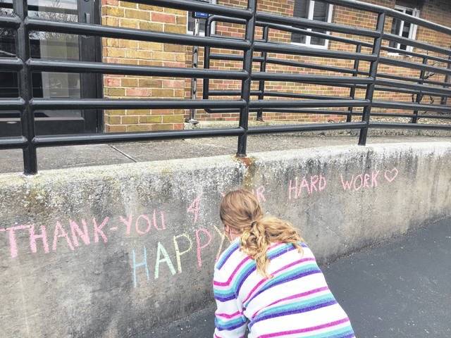 Jazahera Moore recently visited Arbors at Pomeroy, placing flowers in the windows of residents and writing messages with sidewalk chalk.