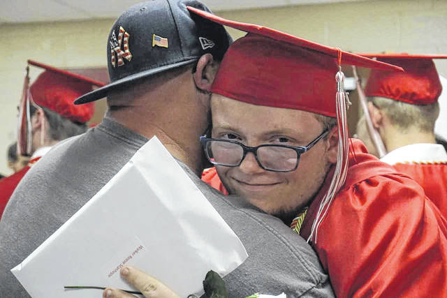 2019 Wahama graduate Walker Stanhope was all smiles after last year's commencement exercises, while getting a hug from his father.