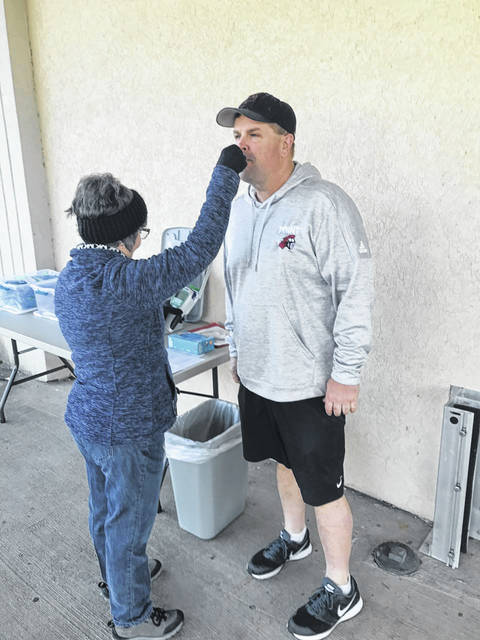 Lydia Gordon, a nurse with Mason County Schools, takes the temperature of Kent Price from PPJ/SHS before food deliveries this week. The temperatures of all workers helping with food delivery were taken as a safety precaution.