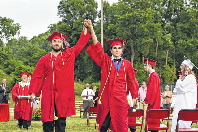 Nicholas Andrew Brewer, left, and Hunter Christian Board join hands in triumph as they exit graduation at Wahama on Saturday. (Mindy Kearns | Courtesy)