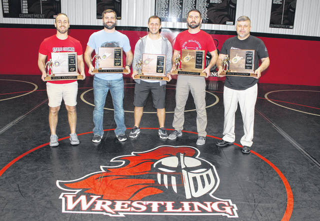 From left, Point Pleasant wrestling coaches David Bonecutter, James Casto, John Bonecutter, Jed Ott and George Smith hold the five Class AA-A state titles won by the program over the past 11 years inside the Hartley Wrestling Building on Thursday, March 5, in Point Pleasant, W.Va.