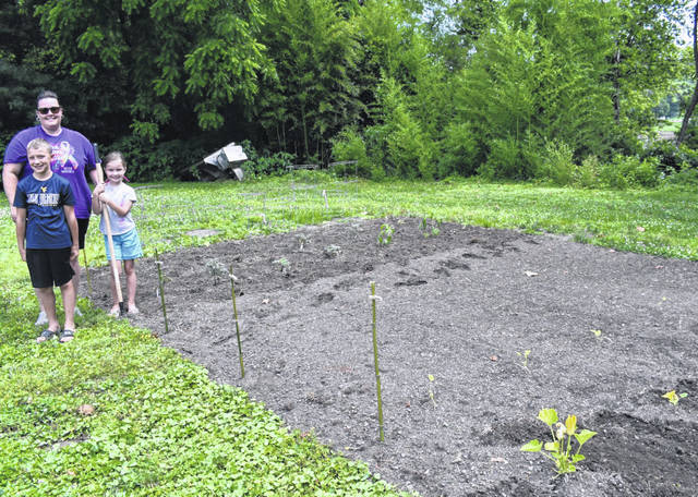A town-sponsored community garden has been planted in Hartford, near the water office. Pictured are Councilwoman Natalie Greene, her daughter Mattie, and Harrison Lloyd, as they get ready to plant bean seed. (Mindy Kearns | Courtesy)