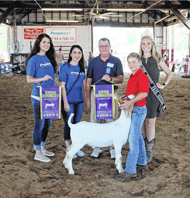 Pictured is Nathan Wood who showed the grand champion market goat sold at the 2019 Mason County Fair. Also pictured, buyers from APG and People's Bank, as well as Fair Queen Marlee Bruner. (Ashley Durst | Courtesy)