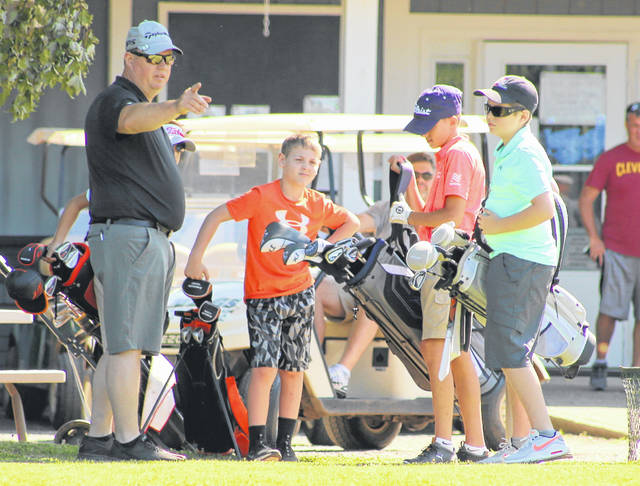 Meigs Golf Course owner and MGC Junior League Director Tom Cremeans, left, gives instruction to a handful of golfers before teeing off on the first hold during a June 25 round in Pomeroy, Ohio. (Bryan Walters OVP Sports)