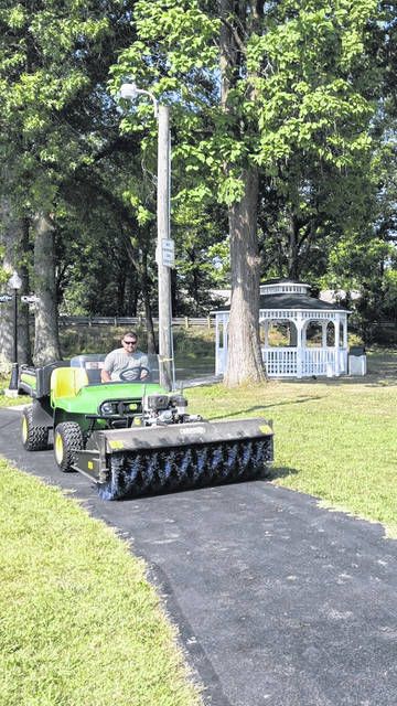 Pictured is City of Point Pleasant Worker Michael Fetty demonstrating the tractor-sweeper cleaning of the Robert & Louise Claflin Walking Trial.