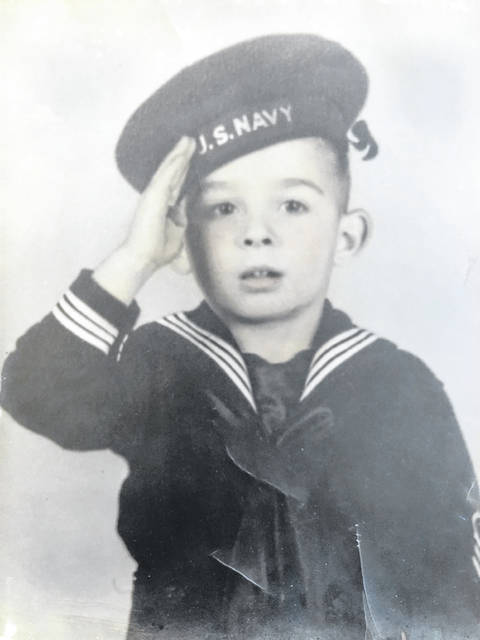 Bill Wood is pictured saluting (circa 1941) in a sailor suit bought by his brother, Tudy (Lewis).