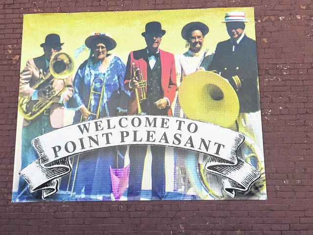 "Some familiar faces have shown up on a banner in downtown Point Pleasant. Pictured from left are the late Paul Wood, Darlene Haer, the late Jack Fowler, the late Carolin Harris and Charles Humphreys. Humphreys said the group photo was taken 18 years ago during an event along the Ohio River. The banner is now hanging on the side of the building which houses the Coffee Grinder, across from the Mothman statue at Gunn Park, serving as a ""Welcome to Point Pleasant."" (Beth Sergent 