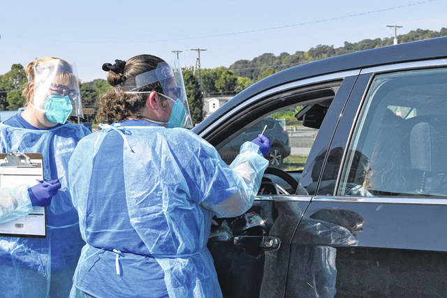 Mason County Health Department Nurse Sherri Nutter, left, and Nurse Manager Jennifer Thomas are pictured as they prepare to test a resident at a free mobile Coronavirus testing site Wednesday in the Bend Area. (Mindy Kearns   Courtesy)
