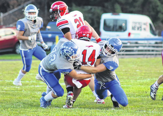 Gallia Academy defenders Zach Belville (13) and Zack Hemby (7) gang up on Rock Hill's Brayden Friend (14) for a tackle during the first half of Friday night's OVC football contest at Memorial Field in Gallipolis, Ohio.