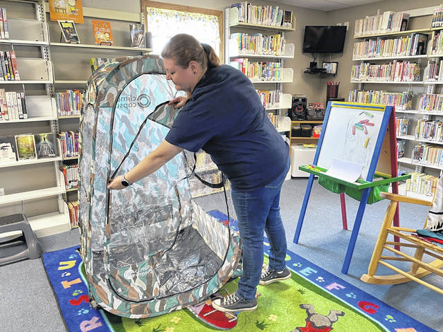 Mason County Library employee April Scott is shown as she opens one of six sports pods that story hour children in Mason will use to maintain social distancing. Different fun methods will be used at each library to keep the participants apart. Mason library's theme will be camping, with the children sitting around an imitation campfire. (Mindy Kearns | Courtesy)