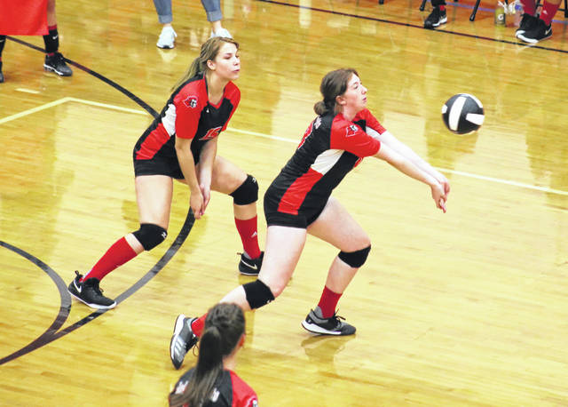 Point Pleasant junior Addy Cottrill bumps a ball in the air as teammate Tristan Wilson looks on during Thursday night's volleyball match against Doddridge County in Point Pleasant, W.Va.