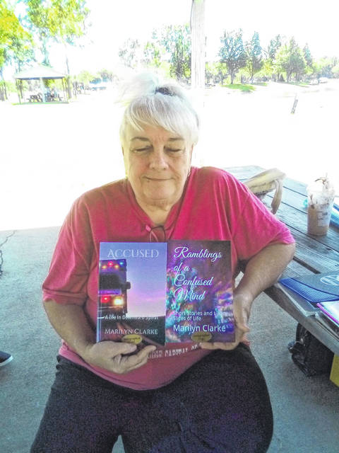 "Marilyn Clarke is pictured with her two newest books, ""Accused"" and ""Ramblings of a Confused Mind."""