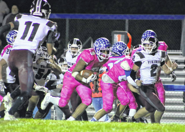 Gallia Academy senior James Armstrong (3) breaks away from a handful of Vinton County defenders during the second half of Saturday night's Division IV, Region 15 second round playoff game at Memorial Field in Gallipolis, Ohio.