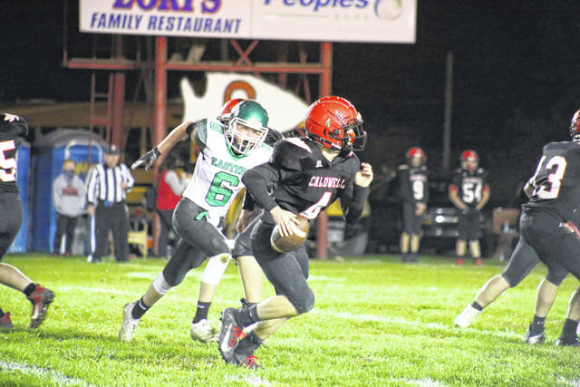 Eastern junior Bryce Newland (6) chases down Caldwell quarterback Braxton Dudley, during the Eagles' playoff victory on Friday in Caldwell, Ohio.