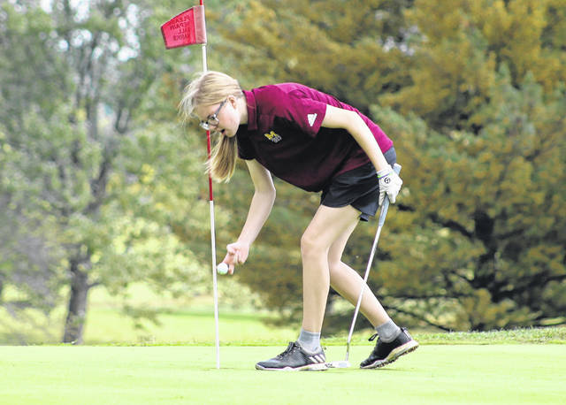 Meigs senior Caitlin Cotterill retrieves a successful putt attempt from the cup during the Division II Southeast Sectional championships held at Franklin Valley Golf Course on Sept. 28 in Jackson, Ohio.