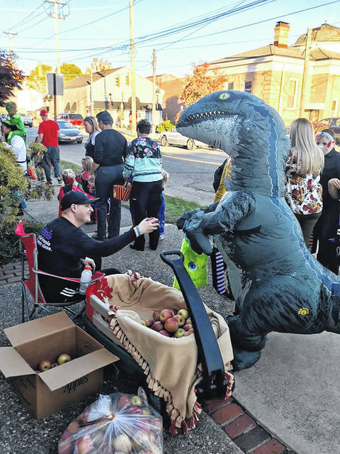 """Derek Henry, wearing a """"Team Ann"""" t-shirt, passes out apples to trick-or-treaters on Third Avenue in Gallipolis in 2019."""