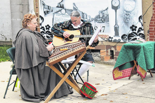 Musicians Kendra Ward and Robert Bence playing Christmas music on hammered dulcimer and guitar for visitors to Main Street during last year's Sugar Plum Stroll. This year, the Main Street Merchants are planning an alternative event called Christmas on Main. (OVP File Photo)