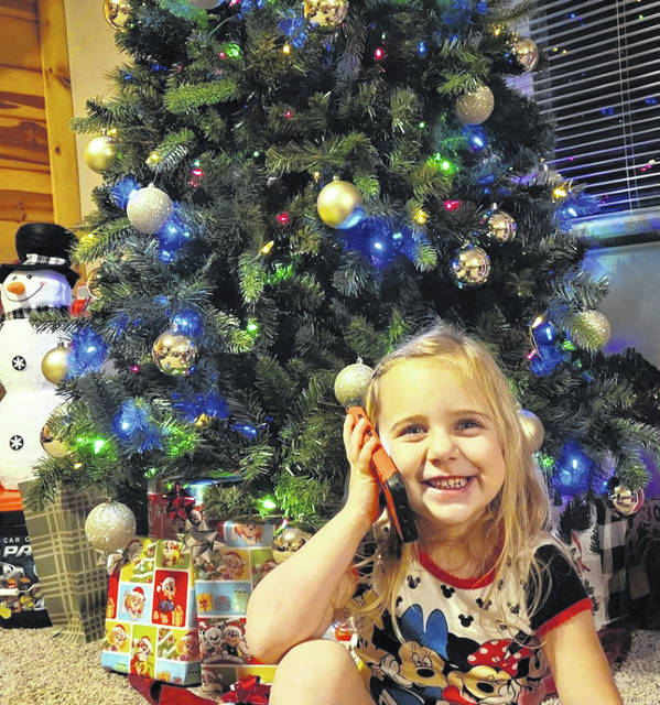 """Kinlee Hudnall, daughter of Jeremy and Brandy Hudnall of New Haven, is pictured as she listens to a Christmas story on """"Dial A Story,"""" a new and free program of the Mason County Public Library System. The number to call for a story, joke, science experiment, and more, is 866-535-9660. (Courtesy photo)"""